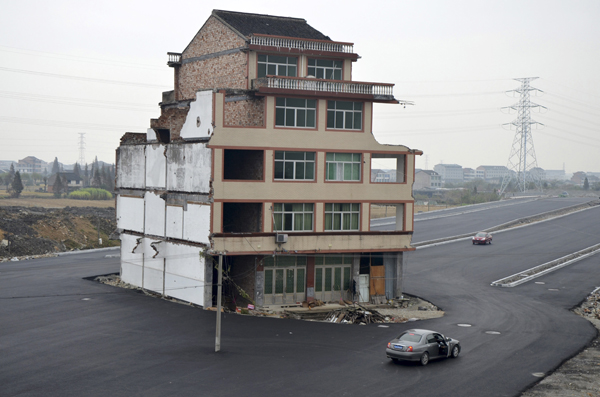 A car stops beside a house in the middle of a newly built road in Wenling, Zhejiang province, November 22, 2012. An elderly couple refused to sign an agreement to allow their house to be demolished. They say that compensation offered is not enough to cover rebuilding costs, according to local media. Their house is the only building left standing on a road which is paved through their village. REUTERS/China Daily